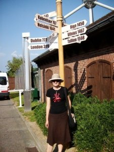 Me with European cities sign post near the Atomium in Brussels
