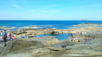 People swimming in a rockpool in Cornwall